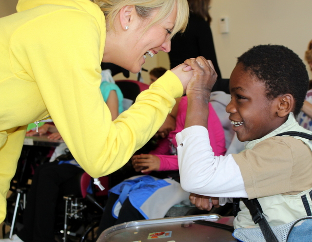 Photo of a child holding a female adult's hand. He is in a wheelchair and she is wearing a bright yellow sweater.