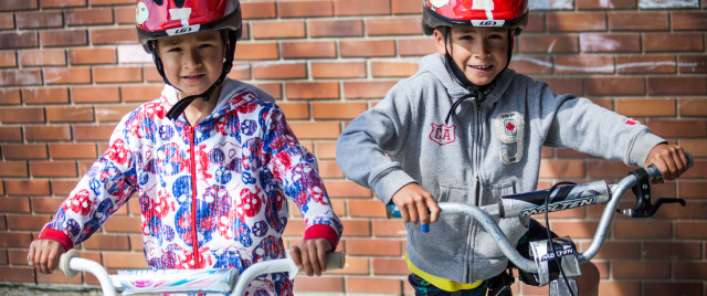 Photo of two brothers riding bikes wearing red helmets.